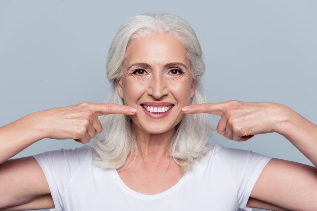 An older woman points to her bright, white smile with both hands